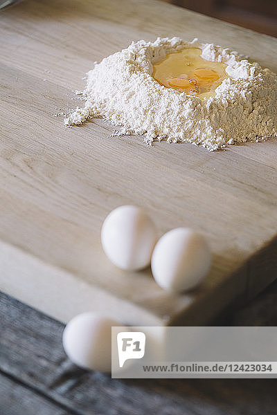 Wheat flower and semolina with egg yolk on pastry board
