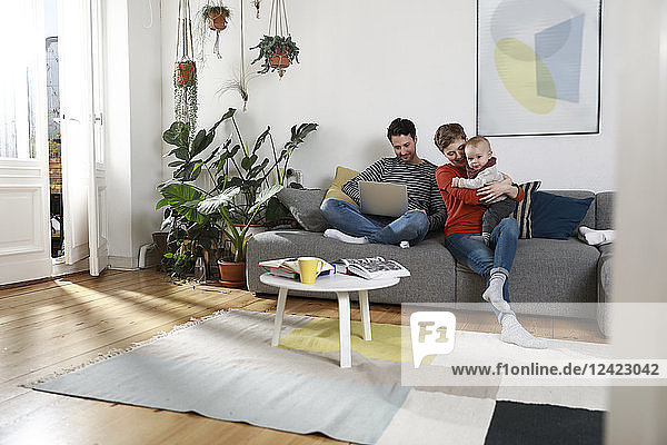 Family sitting on couch  using laptop