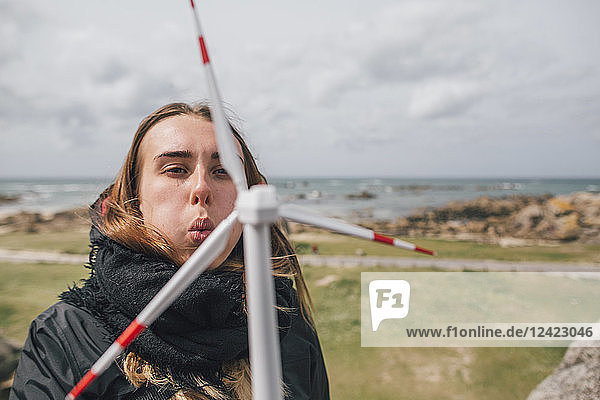France  Brittany  Meneham  young woman with miniature wind turbine at the coast