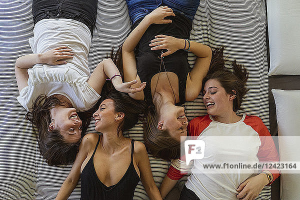 Four friends relaxing on couch at home