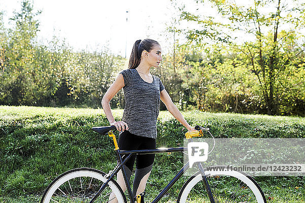 Sportive young woman with bicycle in nature