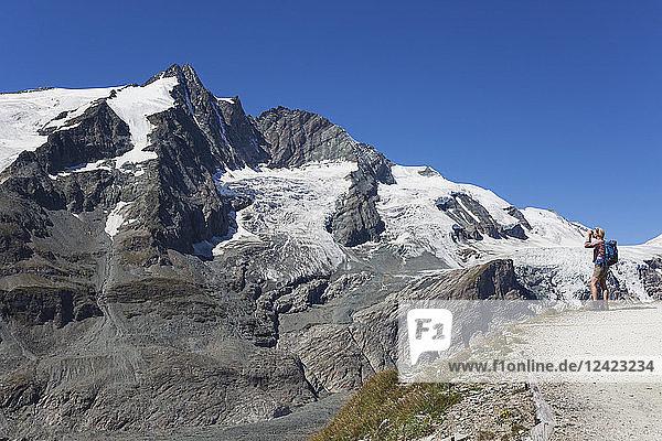 Austria  Carinthia  female hiker with binoculars watching Grossglockner peak  High Tauern National Park