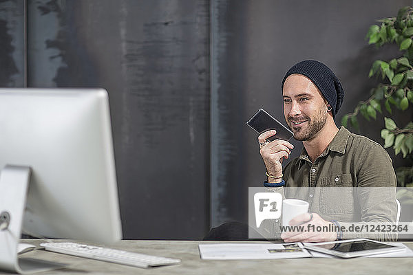 Smiling young man with cell phone at desk in office