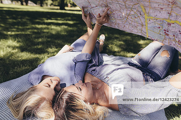 Two young women lying on blanket looking at map in a park