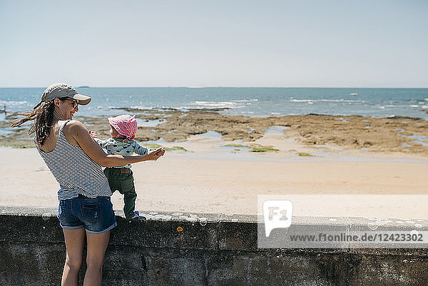 France  mother and baby girl having fun together at beach promenade