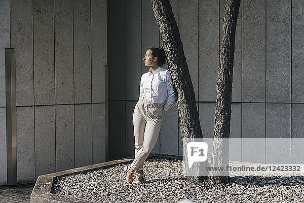 Young businesswoman leaning against atree in a backyard