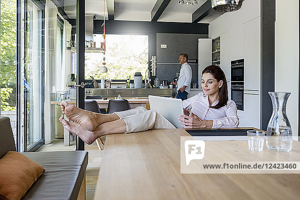 Relaxed woman at home using a laptop at table with man in background