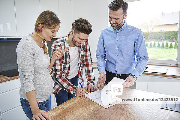 Couple with real estate agent signing contract in kitchen of new apartment Couple with real estate agent signing contract in kitchen of new apartment