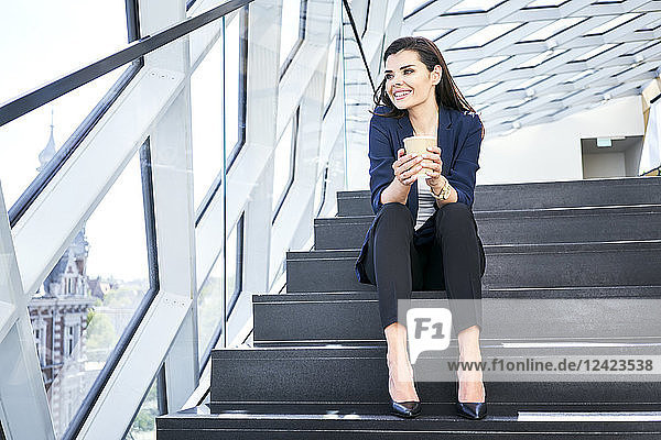 Smiling businesswoman sitting on stairs having a coffee break in modern office