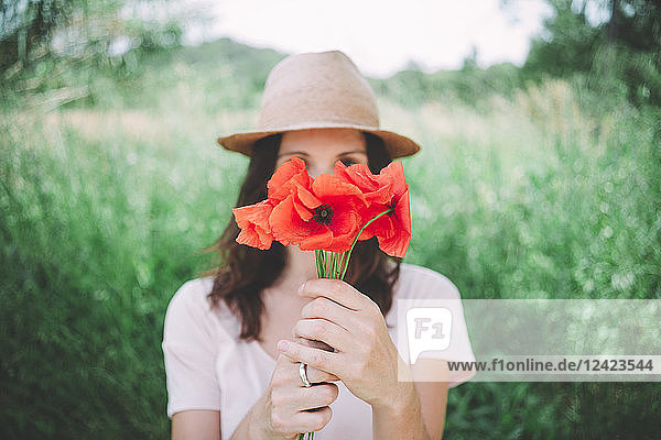 Woman holding a bouquet of red poppies in spring Woman holding a bouquet of red poppies in spring