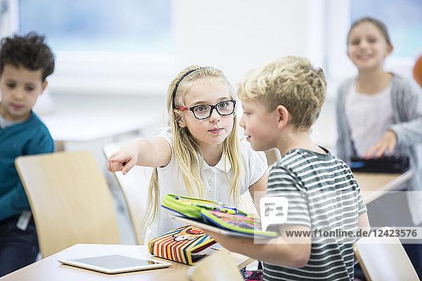 Serious girl rebuking boy in class