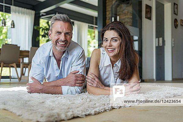 Portrait of happy couple lying on carpet at home