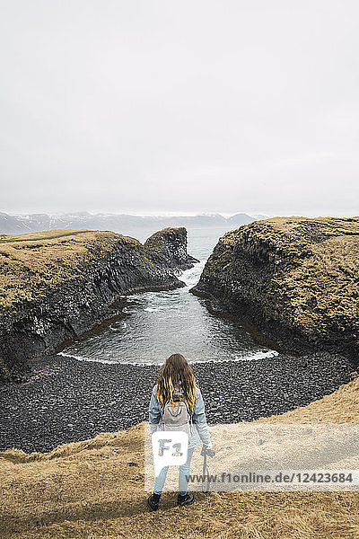 Iceland  back view of young woman with backpack and camera looking at coast