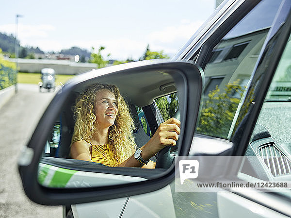 Reflection in wing mirror of smiling woman driving electric car