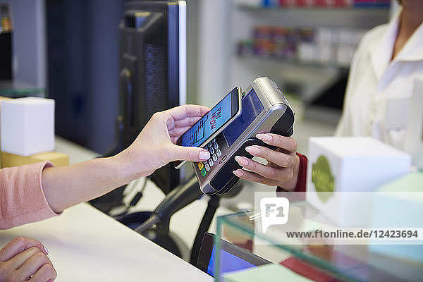 Customer paying cashless with smartphone in a pharmacy
