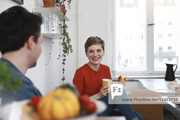 couple sitting in kitchen  talking  woman eating apple couple sitting in kitchen, talking, woman eating apple