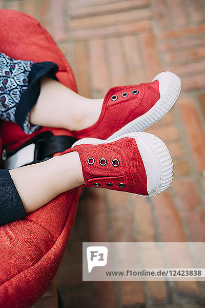 Baby feet with red shoes in the stroller