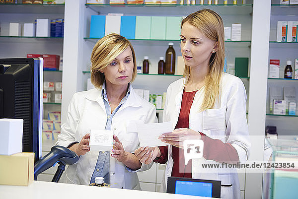 Two pharmacists working together in pharmacy Two pharmacists working together in pharmacy