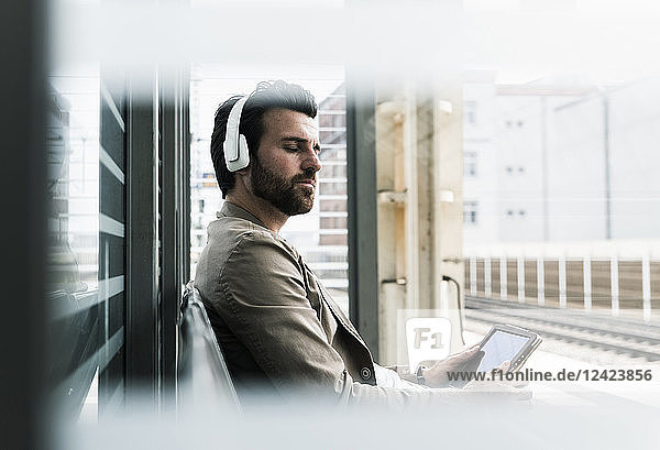 Young man with closed eyes wearing headphones and holding tablet at the station platform
