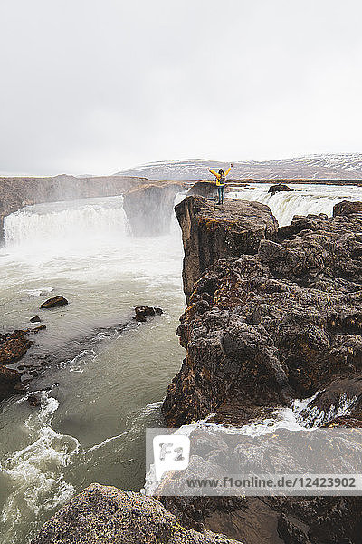 Iceland  woman standing at Godafoss waterfall with raised arms