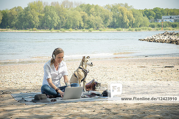 Woman sitting on blanket at a river with dog wearing headphones and using laptop