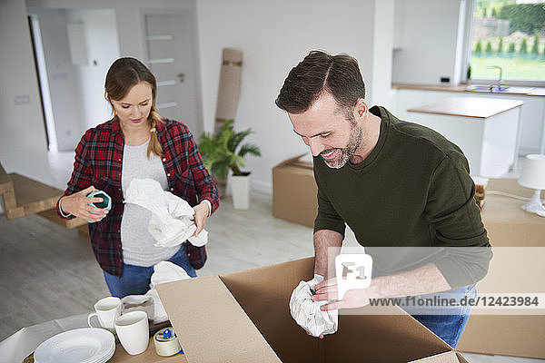 Couple moving house packing their belongings Couple moving house packing their belongings