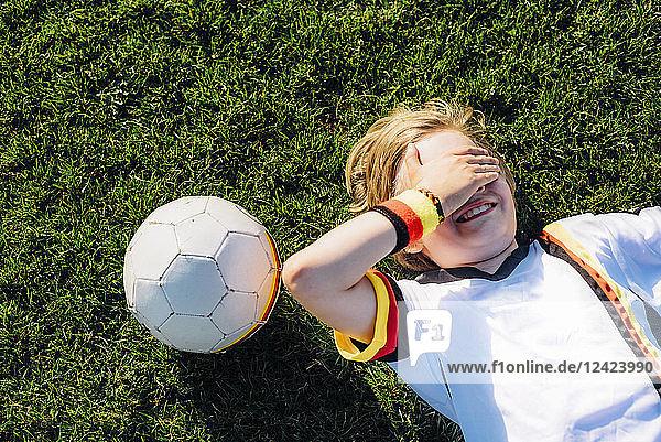Boy in German soccer shirt lying on grass  covering eyes