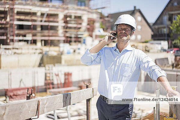 Man wearing hard hat on cell phone on construction site
