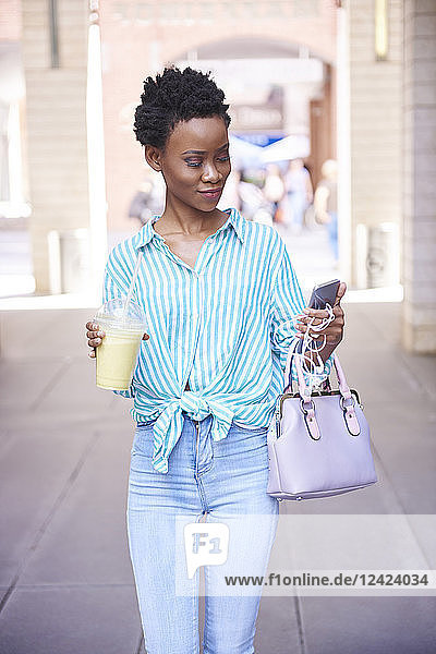 Woman with smoothie looking at cell phone in the city Woman with smoothie looking at cell phone in the city