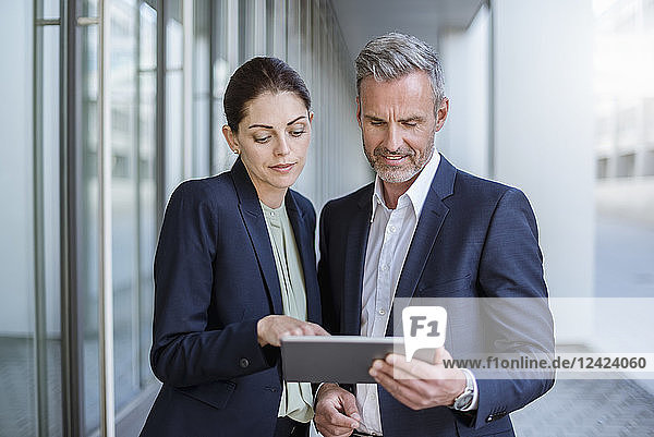 Portrait of two business partners looking together at tablet