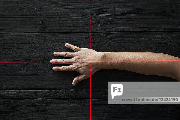 Human hand getting scanned by red light rays