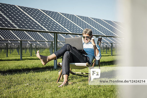 Mature man sitting in beach lounger  using laptop in solar plant