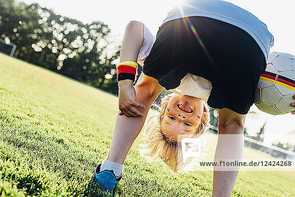 Boy on soccer field  bending over  looking through his legs