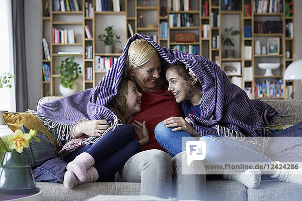 Mother and her daughters cuddling and having fun  sitting on couch  covered in blanket