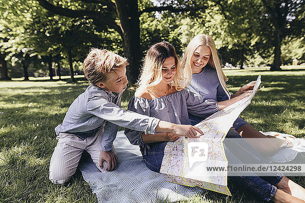 Two young women and a boy looking at map in a park