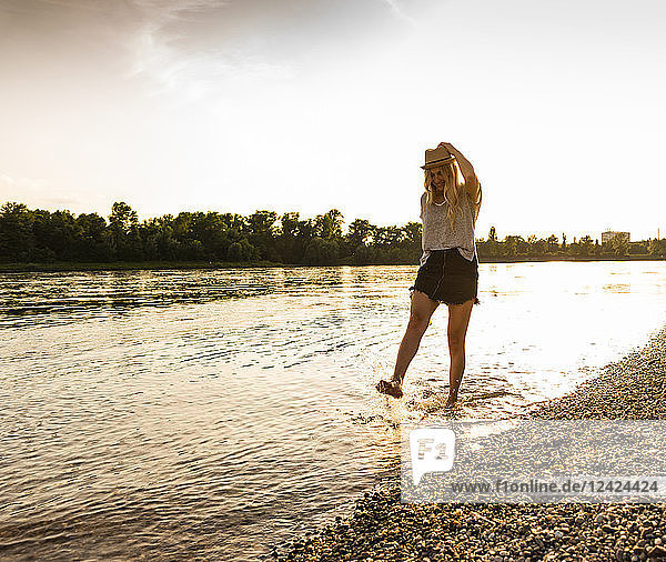 Young woman walking barefoot on riverside in the evening