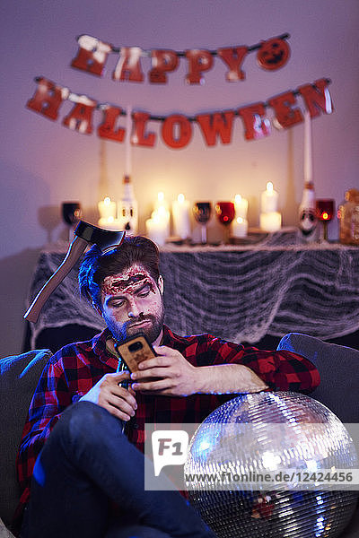 Bored man using mobile phone at Halloween party Bored man using mobile phone at Halloween party