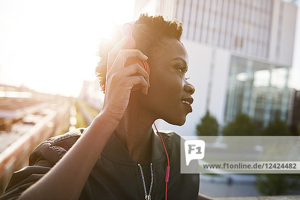 Young woman at backlight listening music with headphones Young woman at backlight listening music with headphones