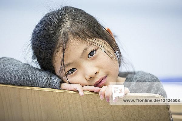 Portrait of schoolgirl on chair in school
