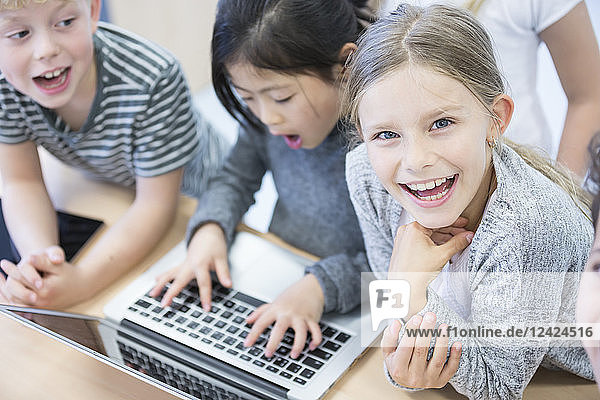 Happy pupils using laptop in class