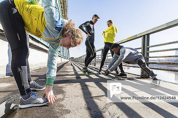 Friends doing stretching exercise on bridge in the city