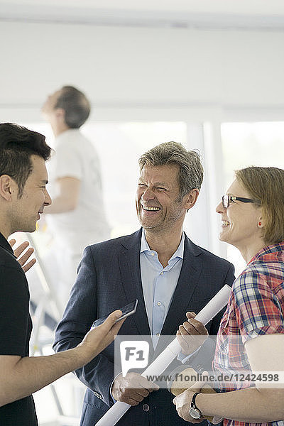 Happy man in suit and couple talking in unfinished building