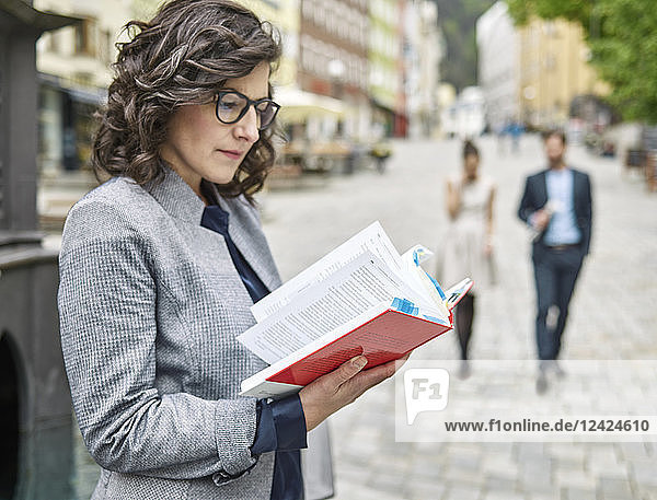 Businesswoman reading book in the city