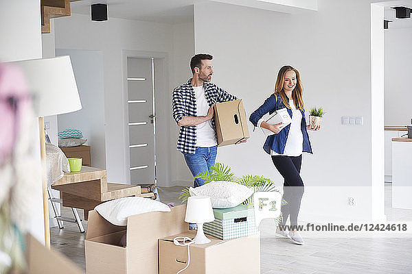 Couple moving into new flat carrying cardboard box and plant
