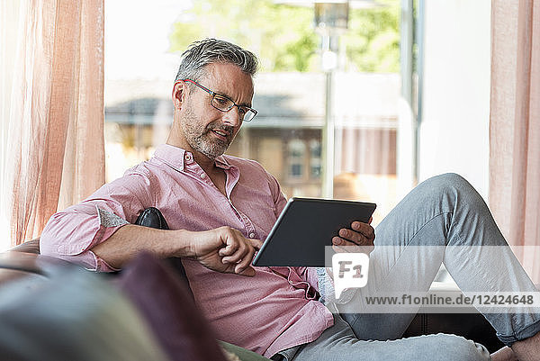 Mature man sitting on couch at home using a tablet