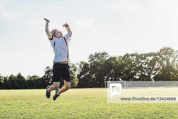 Boy wearing German football shirt playing soccer