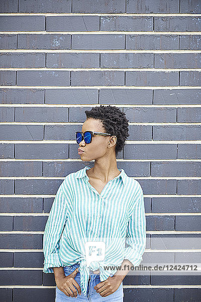 Woman with sunglasses standing in front of grey facade waiting