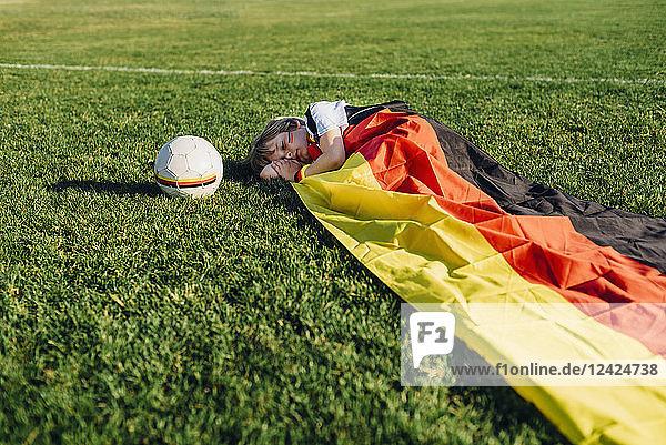 Boy sleeping on soccer field  covered iwith German flag
