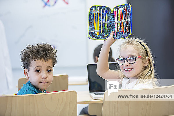 Portrait of schoolboy and schoolgirl with laptop and pencil case in class