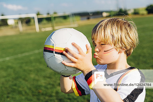 Boy with face paint and German football shirt  kissing soccer ball